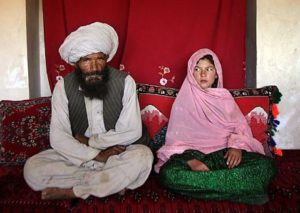 Portrait of soon to be wed Faiz Mohammed, 40, and Ghulam Haider, 11, at her home in a rural village of Damarda in Ghor province. Ghulam said she is sad to be getting engaged as she wanted to be a teacher. Her favorite class was Dari, the local language, before she was made to drop out of school. Married girls are seldom found in school, limiting their economic and social opportunities. Parents sometimes remove their daughters from school to protect them from the possibility of sexual activity outside of wedlock. It is hard to say exactly how many young marriages take place, but according to the Afghan women's ministry and women's NGOs, approximately 57 percent of Afghan girls get married before the legal age of 16. In addition, once the girl's father has agreed to the engagement, she is pulled out of school immediately. Early pregnancies also result in an increase in complications during child birth.